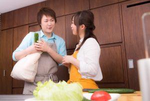 買い出しに行く男性と料理をする女性
