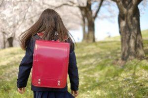ランドセルを背負って桜並木を歩く少女