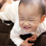 笑顔か泣き顔かわからない赤ちゃん