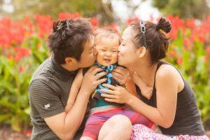 赤ちゃんにキスをするパパとママ