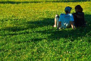芝生の上で語り合う男女
