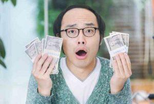 お金を持って驚く男性
