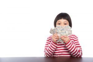 お金を持ちこちらを見る女の子