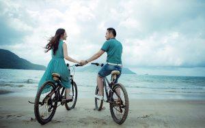 海辺で手を繋ぐ自転車に乗ったカップル