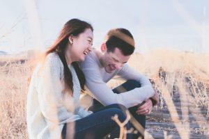 秋の草原で笑顔のカップル