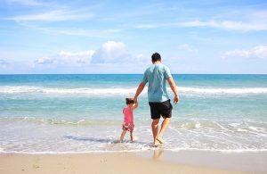 海辺を歩く父と娘