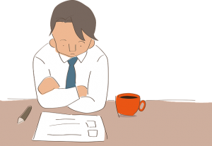 コーヒーを飲みながら勉強をする男性