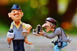 偉そうなアナウンサーとカメラマンの人形