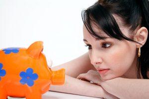 貯金箱を見つめる若い女性