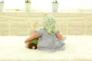 人形と寄り添った後ろ向きの赤ちゃん