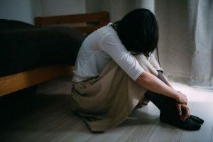 床に座り込み悩む女性