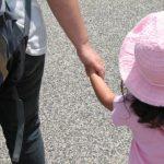 ピンクの服を着た娘と手をつなぐ父