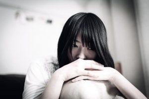 枕を抱えて悩む女性