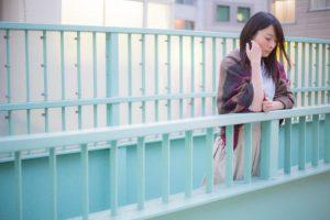 歩道橋の上で悩む女性