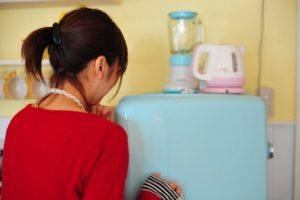 冷蔵庫を開けようとする女性