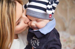 赤ちゃんの頬にキスをするママ