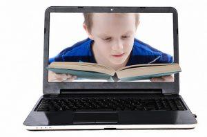パソコンの画面に映る本を読む少年
