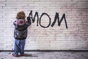 壁にママと書く少年