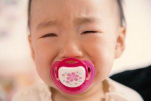 おしゃぶりをくわえて泣く赤ちゃん
