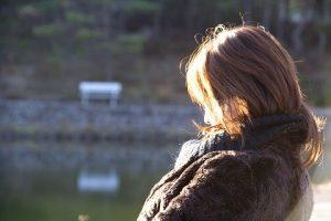 湖のほとりで佇む女性
