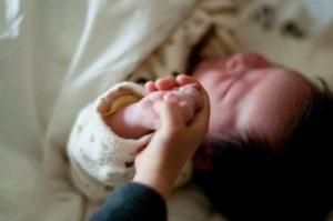 寝ている赤ちゃんの手を握る兄