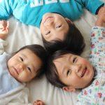 手をつないで仰向けで寝ている3人の子供