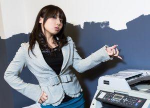 コピー機を指さす女性