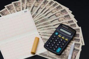 通帳と電卓と1万円札