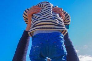 脇に手を入れられ抱えられる赤ちゃん