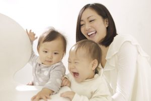 赤ちゃんと机で遊ぶママ