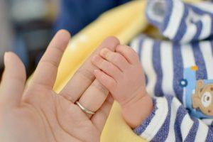 ママの指をつかむ赤ちゃんの手