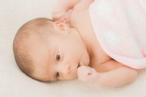 横を向いて指しゃぶりをする赤ちゃん