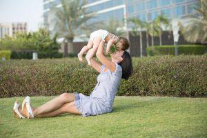 芝生の上で赤ちゃんを掲げるママ