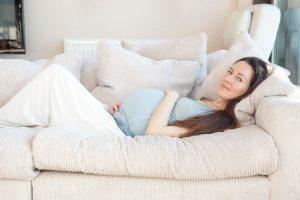 ソファで横になる妊婦