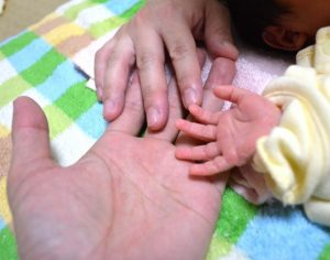 父の手をにぎる赤ちゃん