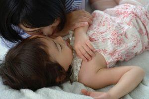 2歳の娘と一緒に寝る母