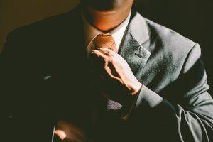 オレンジのネクタイのスーツの男性